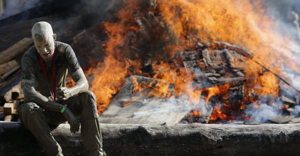 Competidor sujo de lama descansa próximo a uma enorme fogueira após completar os 50 km de um cross country tradicional na Áustria