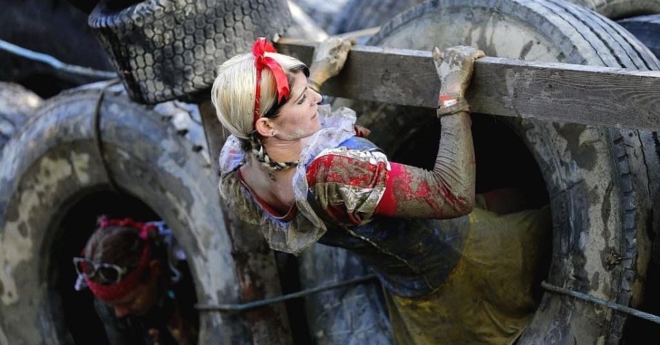 Competidora austríaca passa por obstáculos na prova de 50 km realizada na lama, uma tradição anual na região de Obertriesting