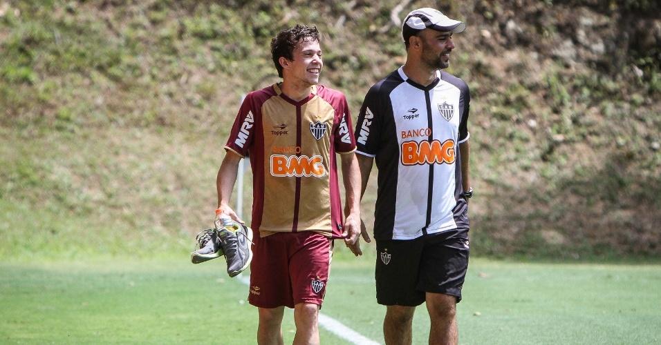 Sorrindo, Bernard observa do lado de fora o treino recreativo do Atlético-MG (20/10/2012)