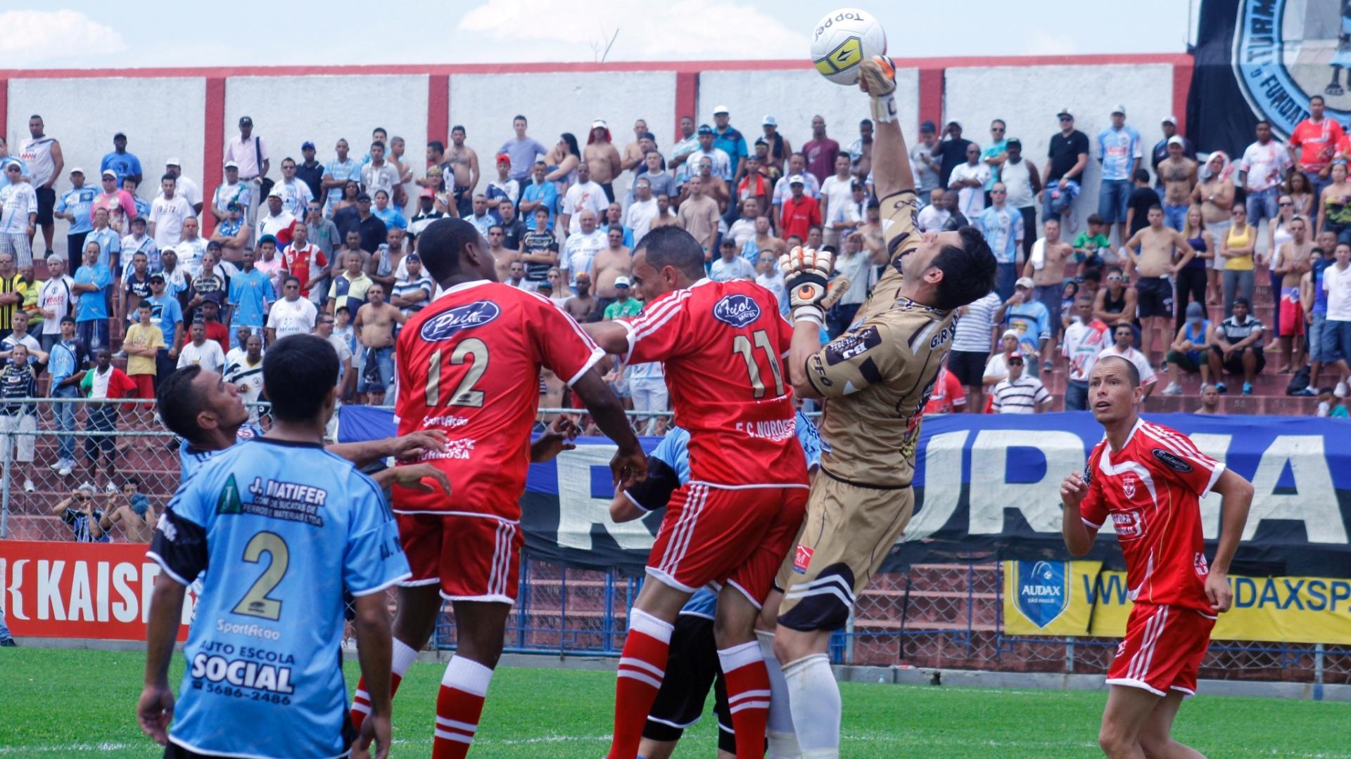 Dentro da área, jogadores de Turma do Baffo (de azul) e Noroeste disputam pela bola durante semifinal da Copa Kaiser