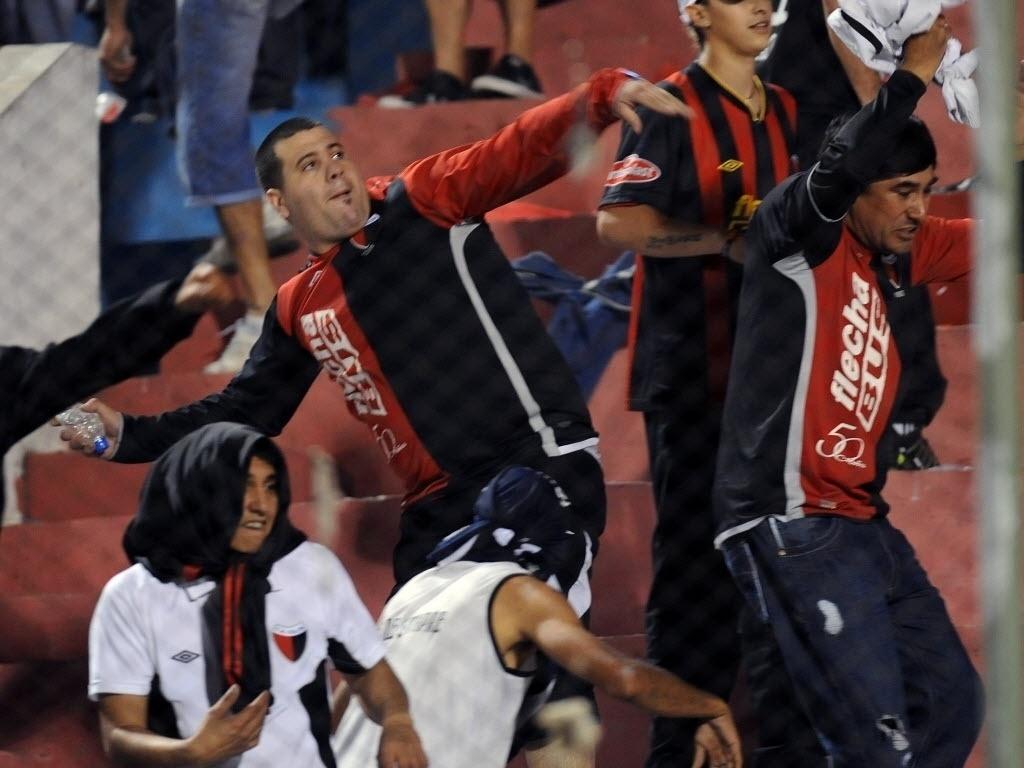 Torcedores do Colón se envolveram em confusão no jogo contra o Cerro Porteño; na foto, um deles se prepara para arremessar uma garrafa no setor adversário