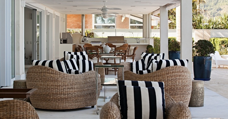 A confortável varanda da Casa Tabatinga - com projeto da arquiteta Selma Tammaro - percorre toda a fachada junto à piscina, voltada para o mar. O ambiente conta com espaço gourmet (ao fundo) e preguiçosas poltronas de fibra natural estofadas em tecido resistente às intempéries