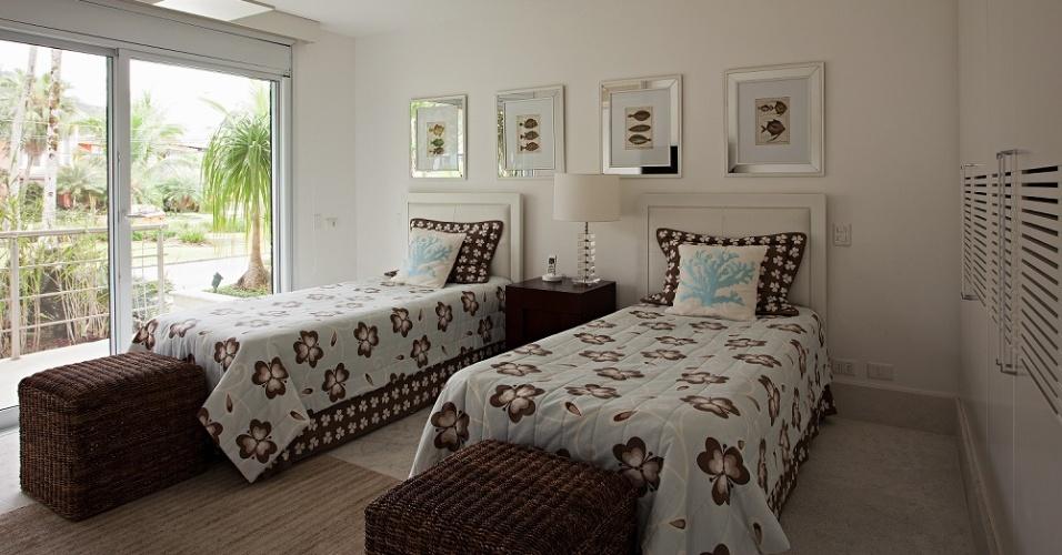 Com varanda e quadros sobre as camas, este é um dos nove quartos da Casa Tabatinga, no litoral de São Paulo. A divisão dos dormitórios entre