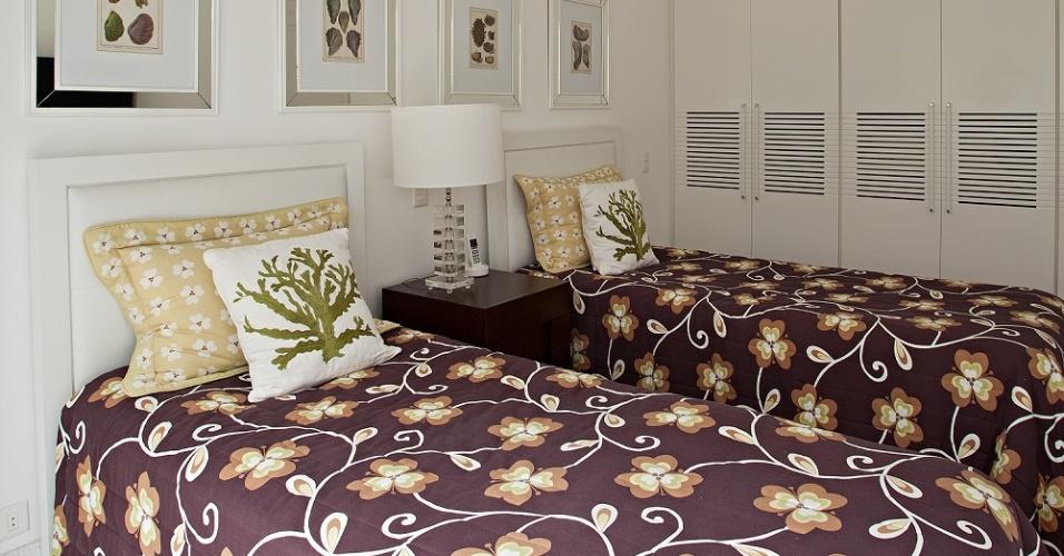 Com armários embutidos e quadros sobre as camas, este é um dos nove quartos da Casa Tabatinga, no litoral de São Paulo. A divisão dos dormitórios entre
