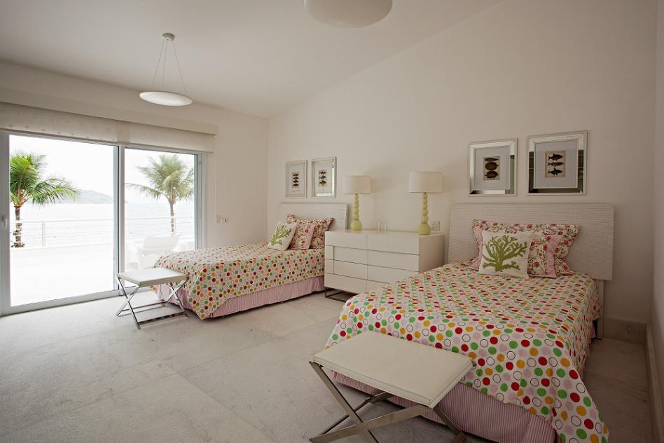 Com piso de mármore branco e quadros sobre as camas, este é um dos nove quartos da Casa Tabatinga, no litoral de São Paulo. A divisão dos dormitórios entre