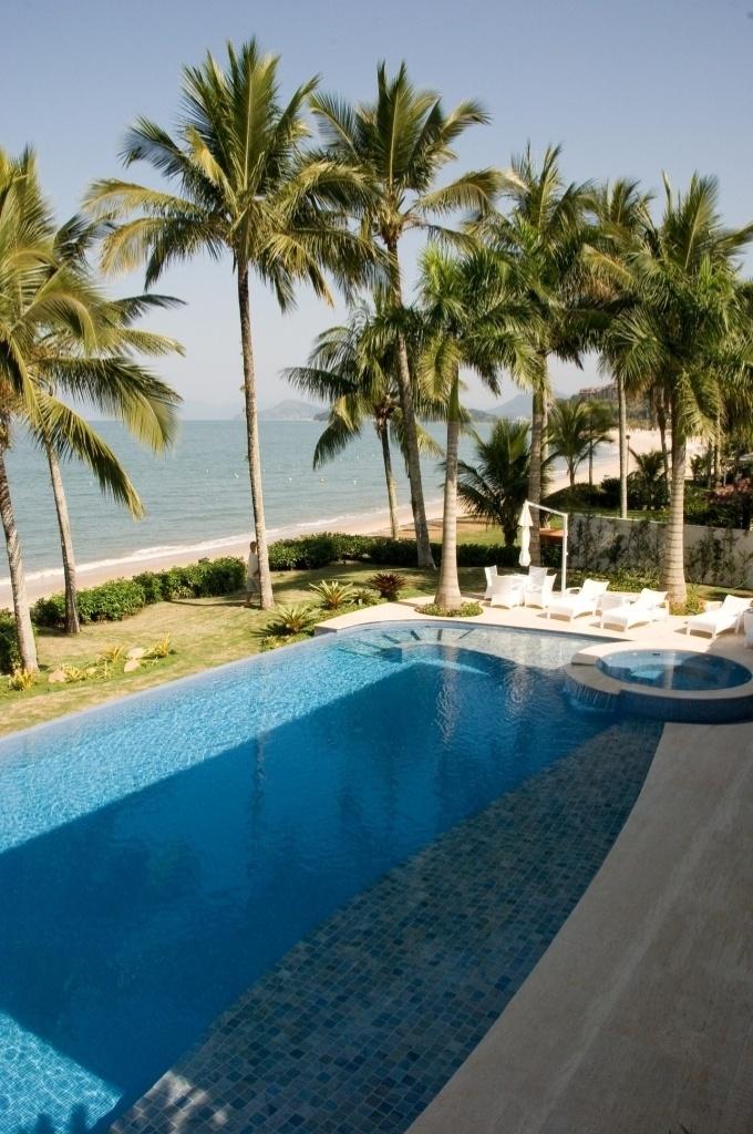 A piscina da Casa Tabatinga, no litoral paulista, é revestida por mármore azul e pastilhas de vidro. Em seu redor estão plantadas palmeiras - entre as quais, imperiais -, cicas e orquídeas. O projeto arquitetônico é assinado por Selma Tammaro