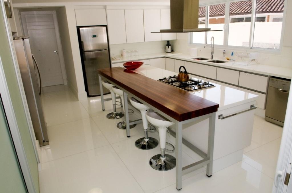 Com chão revestido por mármore composto (cerca de 90% de quartzo e 10% de resinas sintéticas), a cozinha conta com bancada e ilha de cocção central. O projeto da Casa Tabatinga, no litoral paulista, é assinado pela arquiteta Selma Tammaro