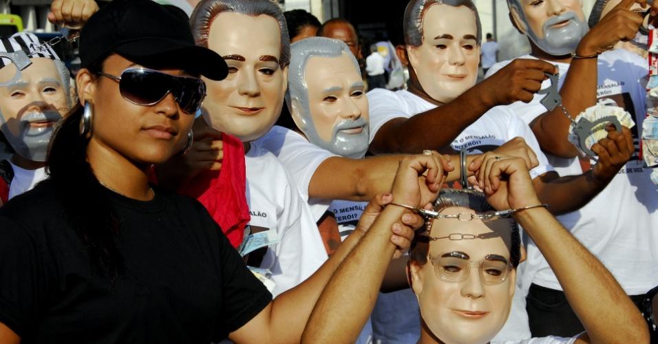 25.out.2012 - Com máscaras dos réus do mensalão, manifestantes participam de um protesto em Niterói, região metropolitana do Rio de Janeiro, para exigir a punição dos envolvidos no caso. A marcha saiu da Câmara de Vereadores e seguiu até a estação das Barcas Arariboia