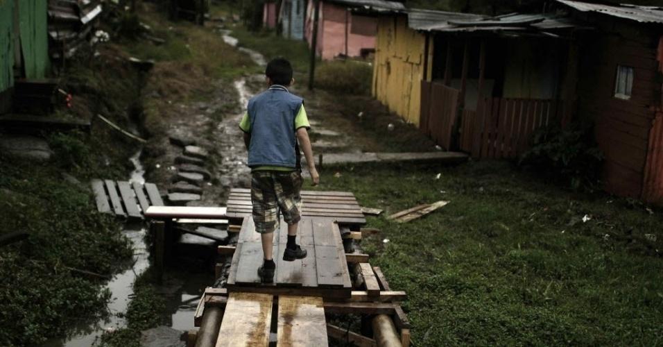 """25.out.2012 - Criança caminha por tábuas de madeira em San José, na Costa Rica. Países latino-americanos enfrentam uma """"epidemia"""" de violência infantil que mata 80.000 crianças por ano, segundo dados informados na Assembleia Geral do Provedor de Justiça Ibero-americana (FIO), realizada na capital costarriquenha"""