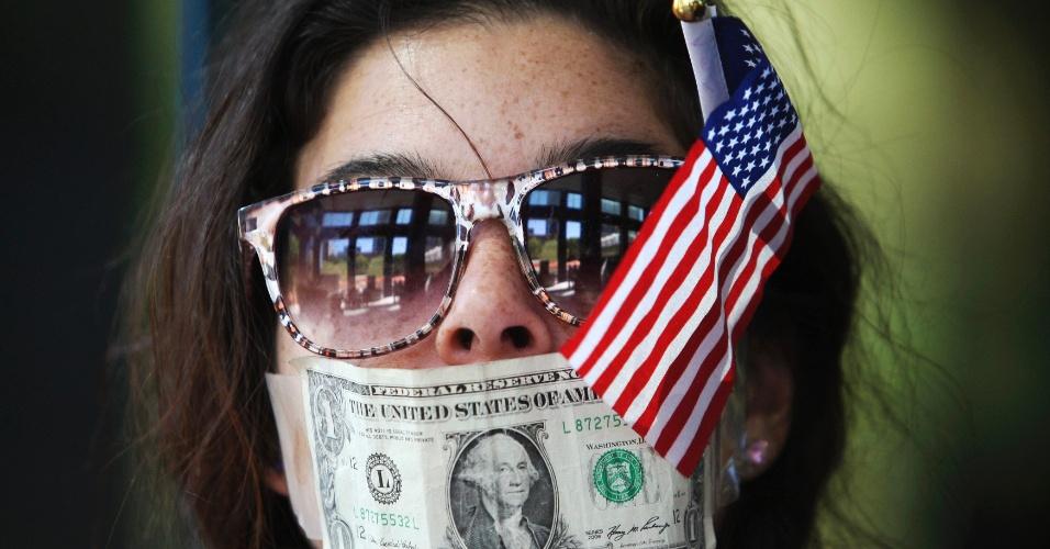 25.out.2012 - Manifestante tapa boca com dólar durante protesto realizado na entrada de uma agência do Citibank em Los Angeles, na Califórnia (EUA). O ato é contra os bancos que não revelam seus gastos com campanhas políticas