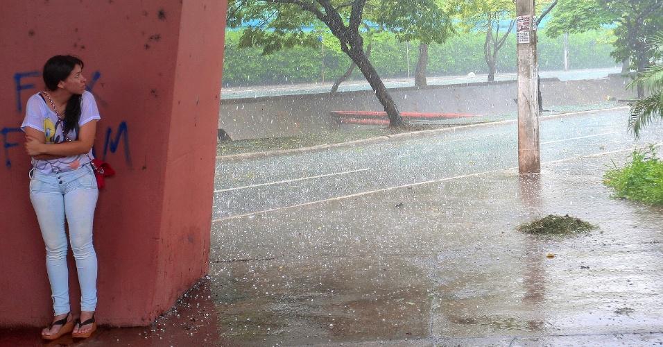 25.out.2012 - Mulher se esconde embaixo de viaduto durante chuva de granizo em Ribeirão Preto, no interior paulista