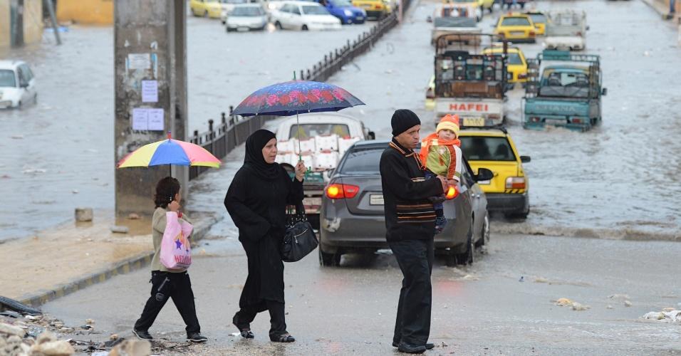 25.out.2012 - Veículos tentam atravessar avenida inundada no norte de Aleppo, na Síria. Rebeldes e membros do governo concordaram em suspender as operações de combate durante o feriado muçulmano, mas ambos também se reservaram o direito de responder a possíveis ataques
