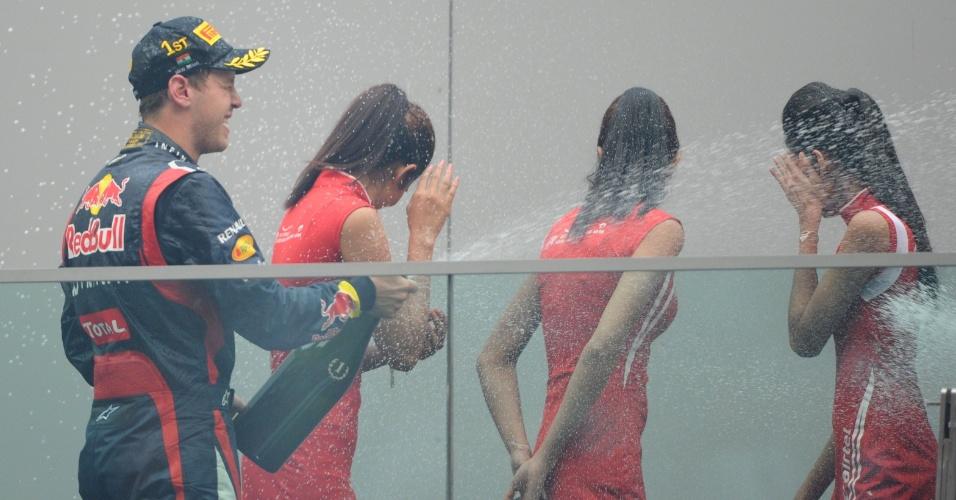 Sebastian Vettel comemora a vitória no GP da Índia atacando champanhe nas grid girls que o acompanharam no pódio