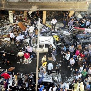 Pessoas se reúnem ao redor do local onde um carro bomba explodiu, em Jaramana, próximo a Damasco