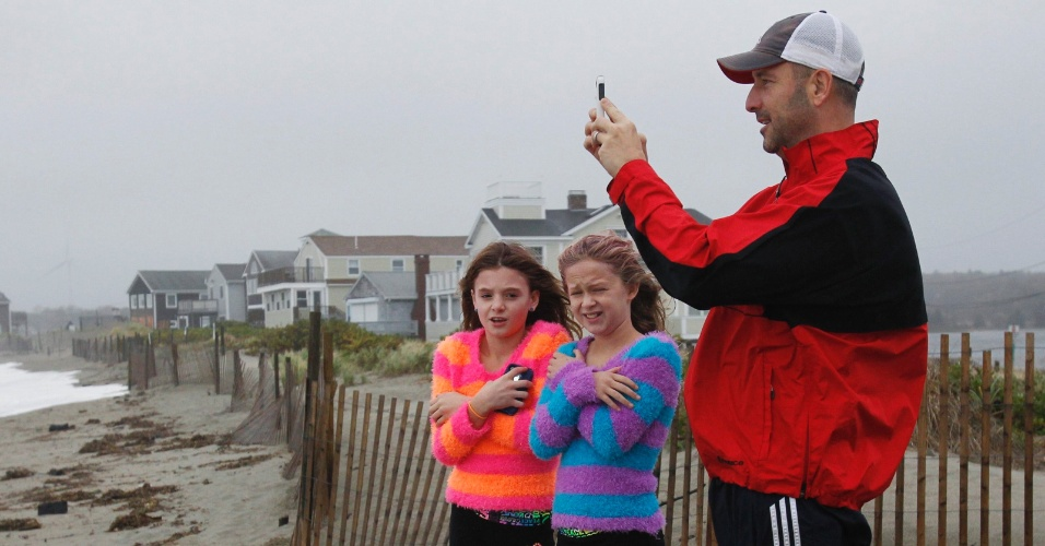 29.out.2012 - Meninas se protegem do vento forte enquanto homem tira fotografia do oceano durante a aproximação do furacão Sandy na costa de Scituate, em Massachusetts, nesta segunda-feira (29). Considerado como uma das piores tempestades a varrer os EUA na história recente, o Sandy provocou o deslocamento de milhares de pessoas e a paralisação do transporte público em várias cidades, bem como o fechamento de escolas e lojas no início desta semana