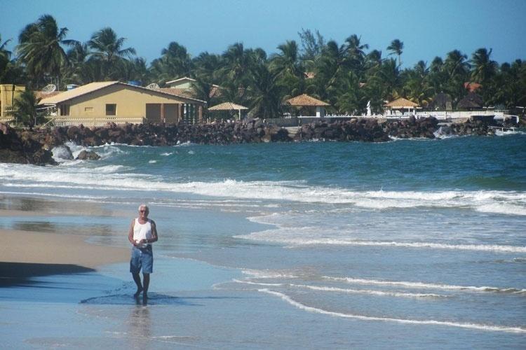 Turista caminha pela areia na Praia do Saco, em Sergipe