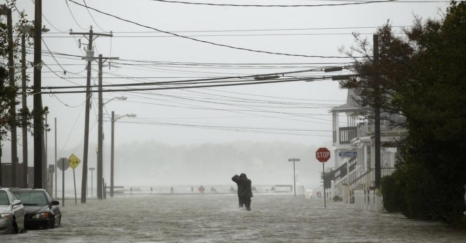 30.out.2012 - Homem atravessa rua inundada de Ocean City, em Maryland, durante a passagem do furacão Sandy pela cidade