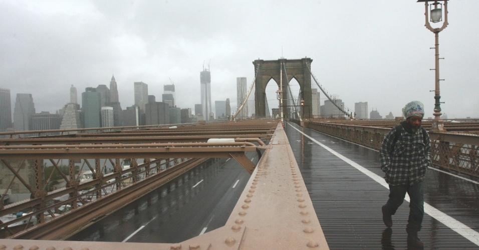 30.out.2012 - Homem caminha pela Brooklyn Bridge, fechada para veículos devido à passagem do furacão Sandy, que deixou a área de Manhattan no escuro