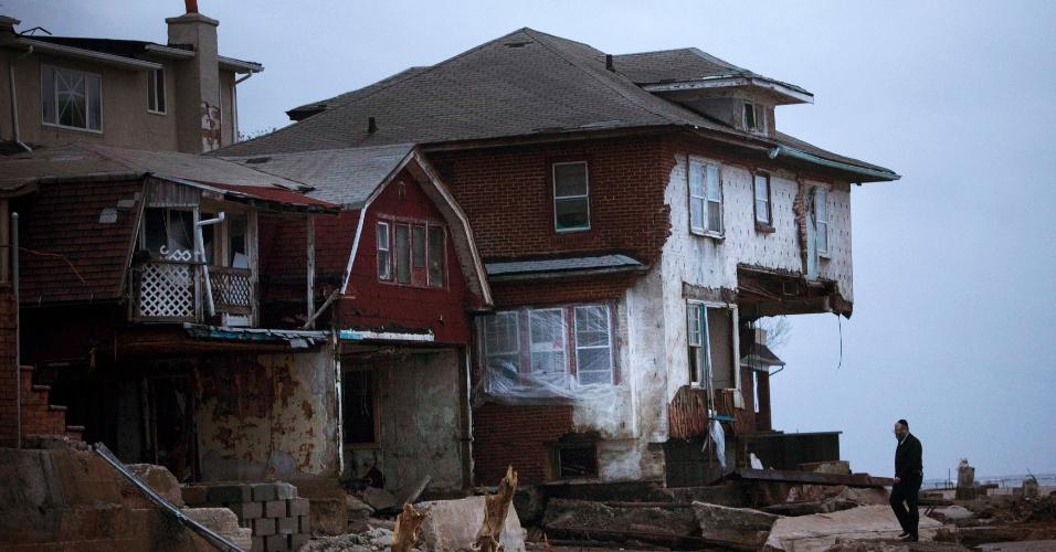 30.out.2012 - Homem observa casa destruída em um condomínio fechado no distrito do Brooklyn, em Nova York. A cidade, costeira, foi a maior entre as afetadas pela passagem do furacão Sandy