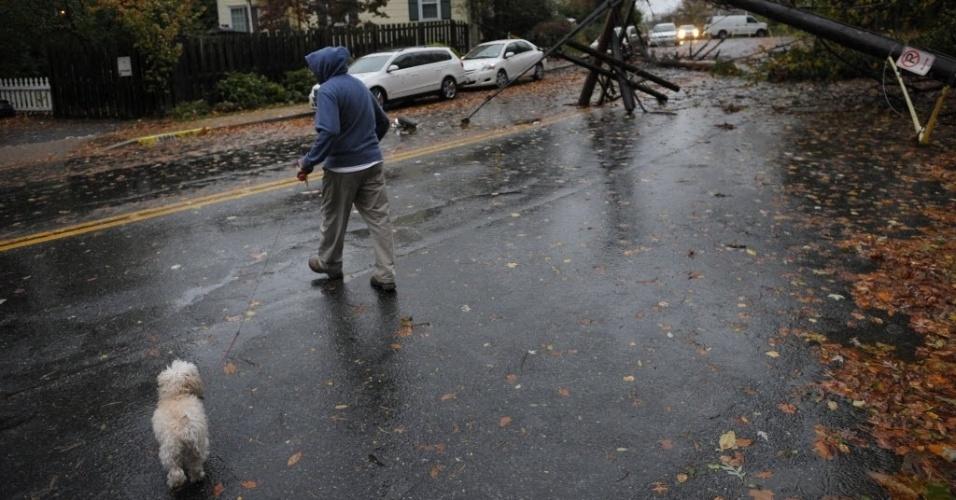 30.out.2012 - Homem passeia com cachorro em área onde postes caíram com a passagem do furacão Sandy, na cidade de Chevy Chase, Estado americano de Maryland