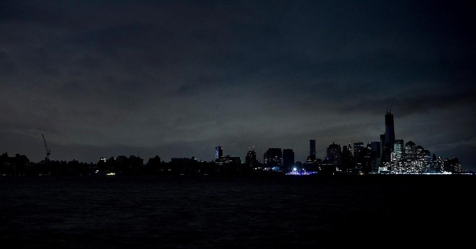 30.out.2012 - Ilha de Manhattan e cidade de nova York vistos de Weehawkin, Nova Jersey, mostram o horizonte escuro, com poucos edifícios iluminados. Cerca de 6 milhões de pessoas tiveram o abastecimento de energia afetado com a passagem do furacão Sandy
