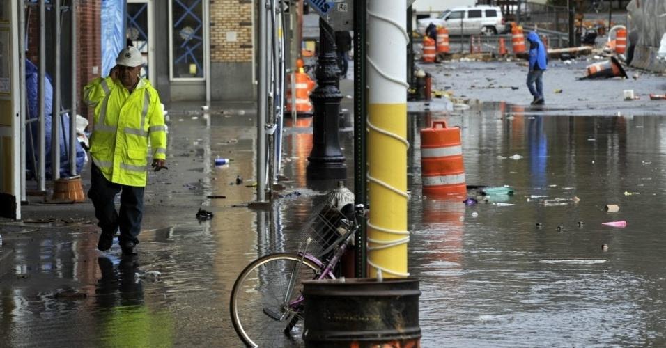 30.out.2012 - Moradores caminham por cenário de devastação em South Street Seaport, área portuária de Nova York inundada pelo furacão Sandy