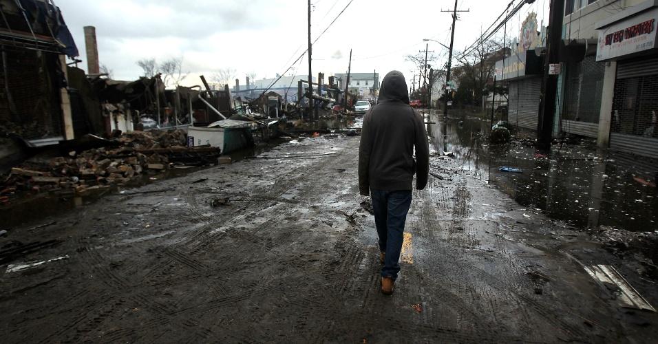 30.out.2012 - Pessoa caminha solitária por rua repleta de destroços e com trechos ainda alagados na região do Queens, em Nova York. A maior cidade dos EUA, costeira, conta 6.000 desabrigados pela passagem do furacão Sandy