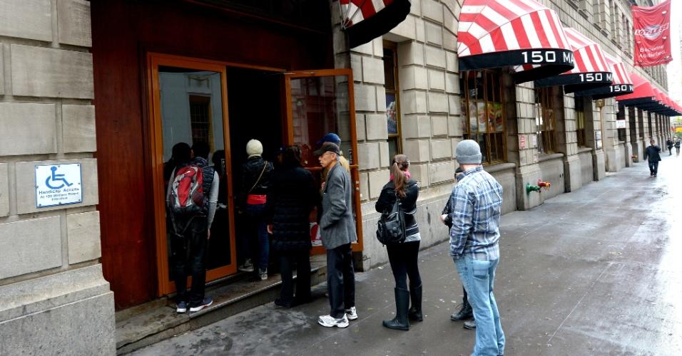 30.out.2012 - Pessoas esperam para comprar alimentos em um dos poucos mercados abertos em Manhattan, Nova York. O furacão Sandy deixou um rastro de destroços e mais de 30 mortos, principalmente nos Estados de Nova York e Nova Jersey, dois dos mais populosos dos EUA, e agora avança, já como tempestade, em direção ao Canadá