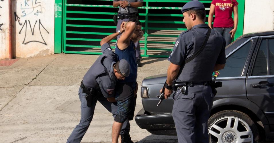 30.out.2012 - Policial militar revista morador durante ocupação da favela de Paraisópolis, na zona sul de São Paulo