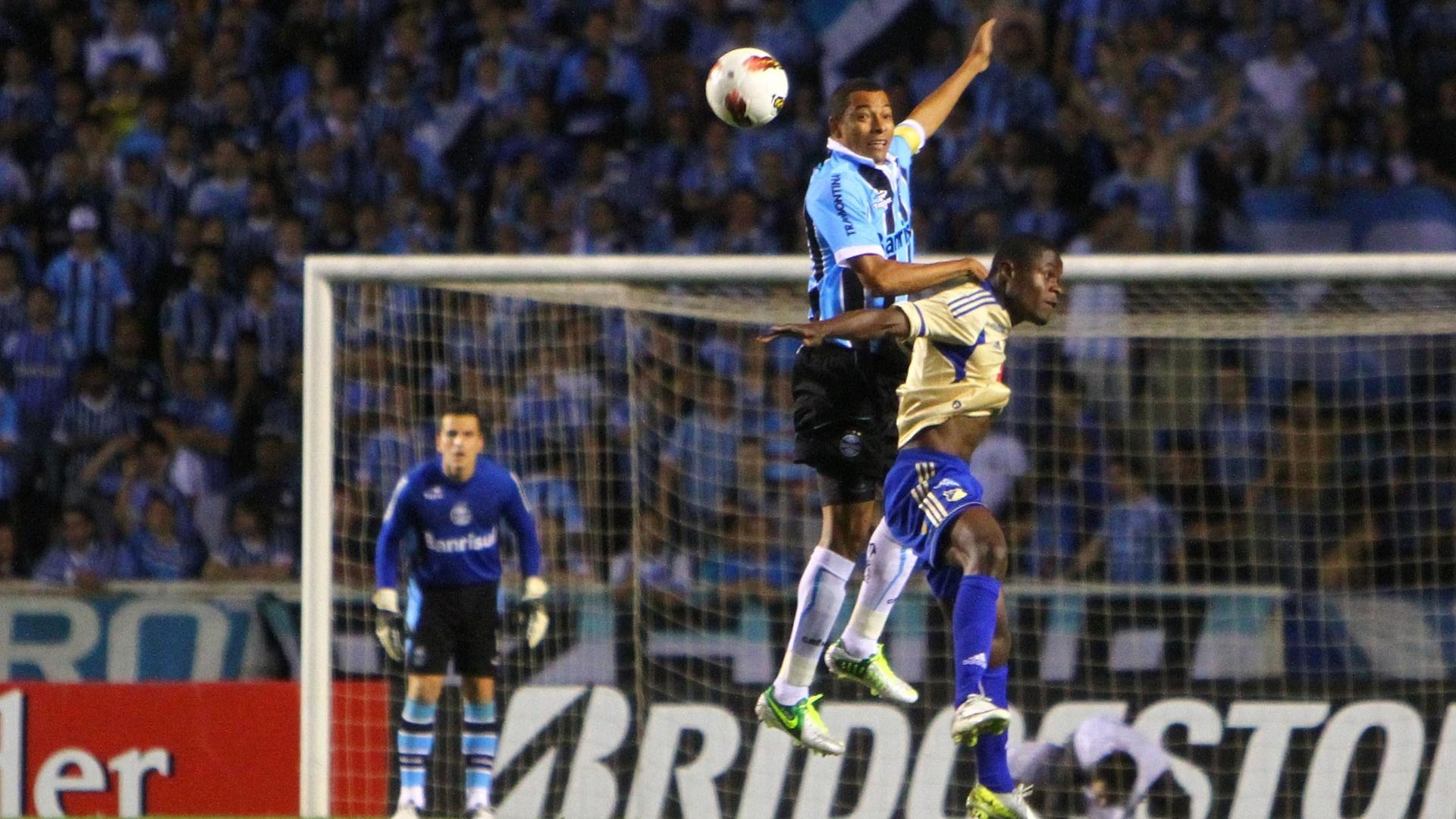 Gilberto Silva sobe para disputar bola no alto com jogador do Millonarios, durante partida no Olímpico