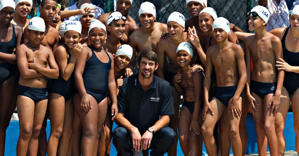 Phelps, dono de 22 medalhas olímpicas, posa para foto com crianças que praticam natação na Vila Olímpica do Complexo do Alemão