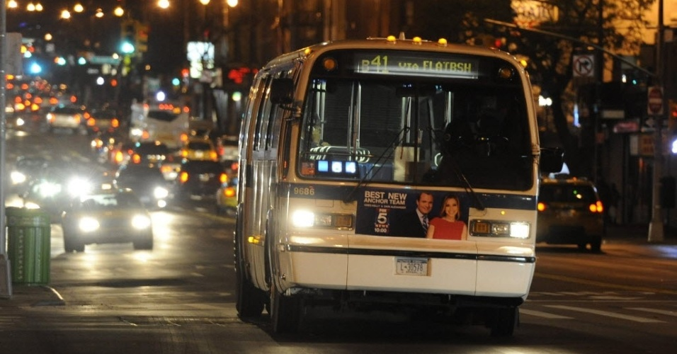 30.out.2012 - Ônibus circula por Nova York na terça-feira à noite. Um dia após a passagem do furacão Sandy, o serviço de ônibus voltou a funcionar normalmente, mas os trens continuam impedidos de circular. Os túneis de Nova Jersey a Manhattan foram fechados
