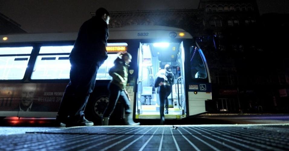30.out.2012 - Ônibus recolhe passageiros, na noite de terça-feira. Um dia após a passagem do furacão Sandy, o serviço de ônibus voltou a funcionar normalmente, mas os trens continuam impedidos de circular. Os túneis de Nova Jersey a Manhattan foram fechados