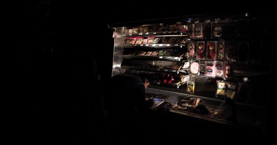 31.out.2012 - Família faz compras no escuro, com auxílio de uma lanterna no mercado Garden of Eden, na cidade de Hoboken, Nova Jersey