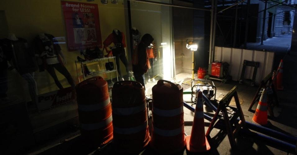 31.out.2012 - Homem acompanha trabalho de bombeamento de água em uma agência bancária alagada, no distrito financeiro de Nova York. A passagem do furacão Sandy pela região deixou grandes áreas de cidade no escuro e alagadas. Nesta quarta-feira (31), os moradores da cidade tentam retomar suas atividades normais