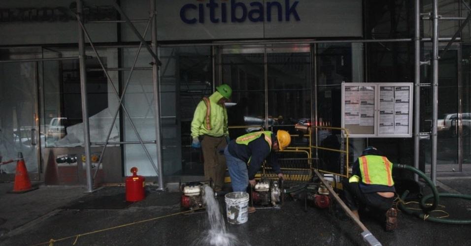 31.out.2012 - Homens bombeiam água de agência bancária alagada, no distrito financeiro de Nova York. A passagem do furacão Sandy pela região deixou grandes áreas de cidade no escuro e alagadas. Nesta quarta-feira (31), os moradores da cidade tentam retomar suas atividades normais