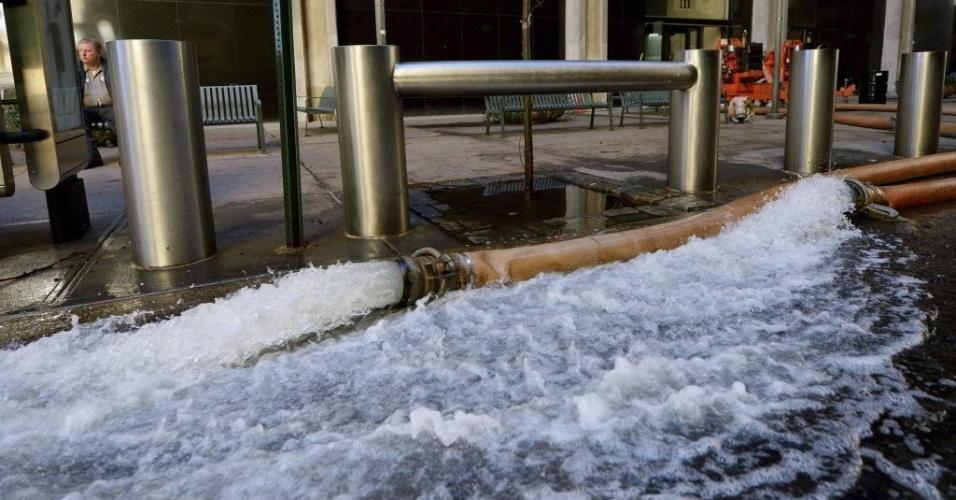 31.out.2012 - Mangueira esvazia sótão de prédio inundado em Wall Street, durante operação de recuperação e limpeza em Nova York, após a passagem do furacão Sandy causar estragos e apagões na cidade