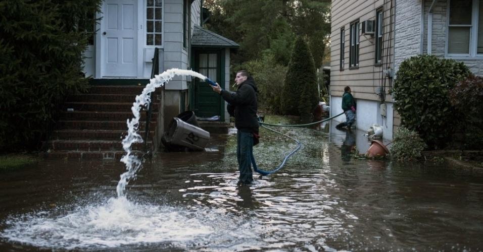 31.out.2012 - Moradores escoam água de dentro de casa em ruas alagadas na cidade de Little Ferry, no Estado americano de Nova Jersey. A passagem do furacão Sandy pela região deixou grandes partes da cidade submersas e sem energia elétrica