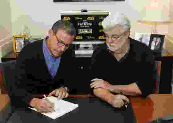 George Lucas assina contrato em que passa a empresa Lucasfilms para a Disney, ao lado de Robert Iger, CEO da Disney, em Burbank, na Califórnia (30/10/12) - AP Photo/Disney, Rick Rowell