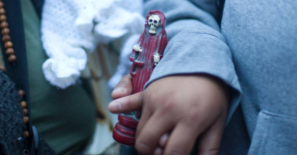 """1º.nov.2012 - Criança segura imagem da """"Santa Morte"""", homenageada no """"Dia dos Mortos"""", em 31 de outubro, no México"""