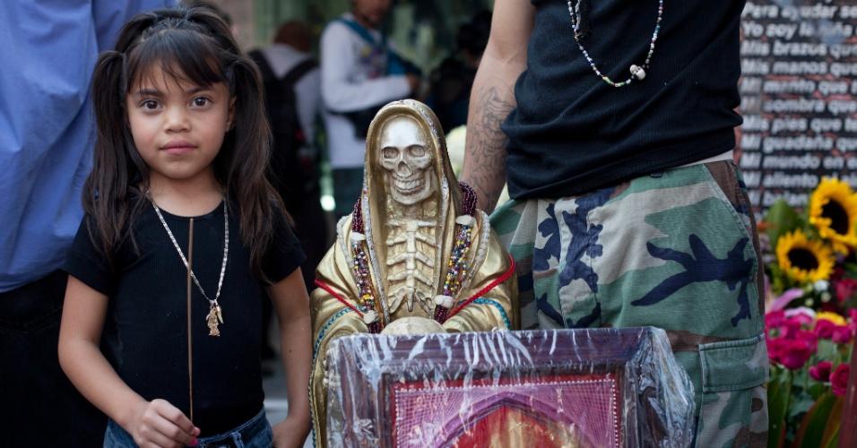 """1º.nov.2012 - Crinaça fica ao lado da imagem da """"Santa Morte"""", homenageada no """"Dia dos Mortos"""", em 31 de outubro, no México"""