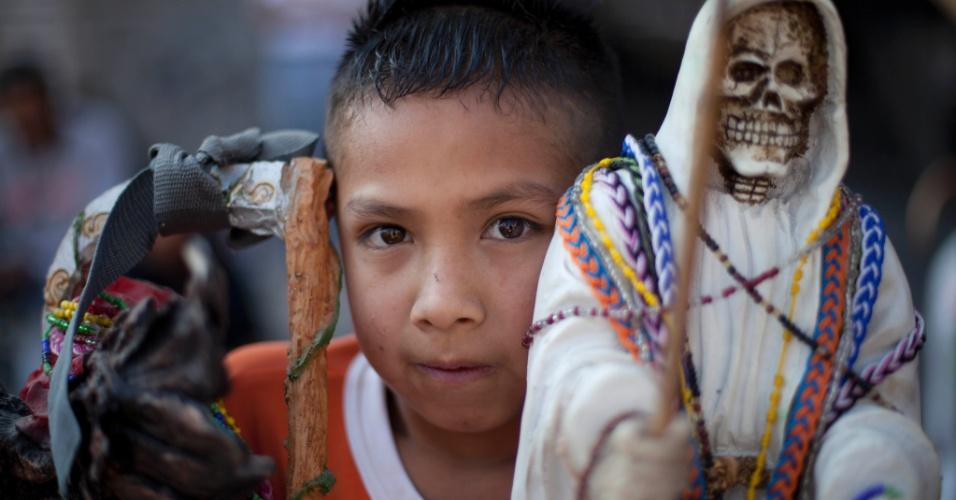 """1º.nov.2012 - Menino segura imagem da """"Santa Morte"""", homenageada no """"Dia dos Mortos"""", em 31 de outubro, no México"""