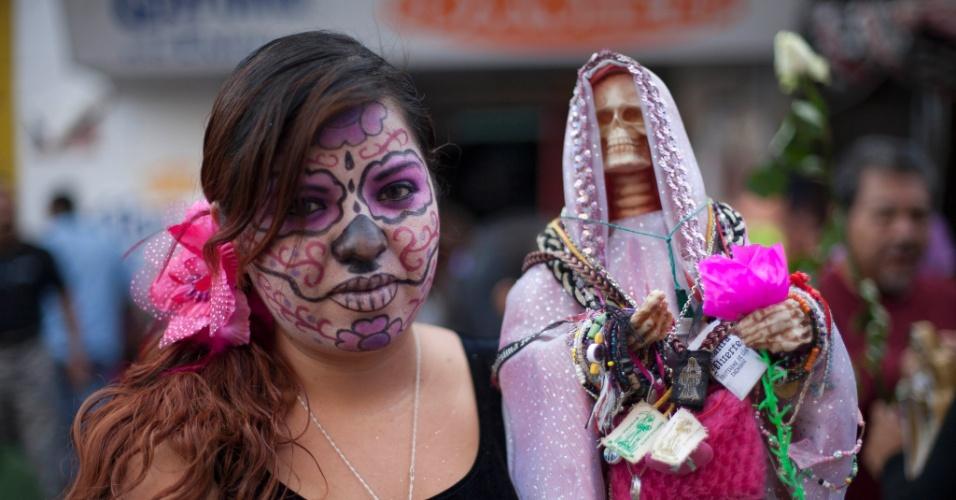 """1º.nov.2012 - Jovem com o rosto pintado segura imagem da """"Santa Morte"""", homenageada no """"Dia dos Mortos"""""""