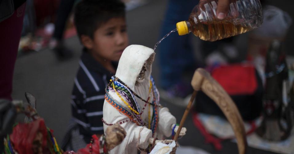 """1º.nov.2012 - Fiel joga tequila sobre imagem da """"Santa Morte"""", homenageada no """"Dia dos Mortos"""""""