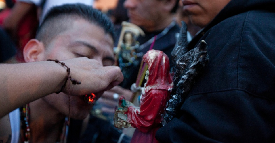 """1º.nov.2012 - Homem fuma maconha como gesto de agradecimento diante de imagem da """"Santa Morte"""", a grande homenageada no """"Dia dos Mortos"""", celebrado em 31 de outubro"""
