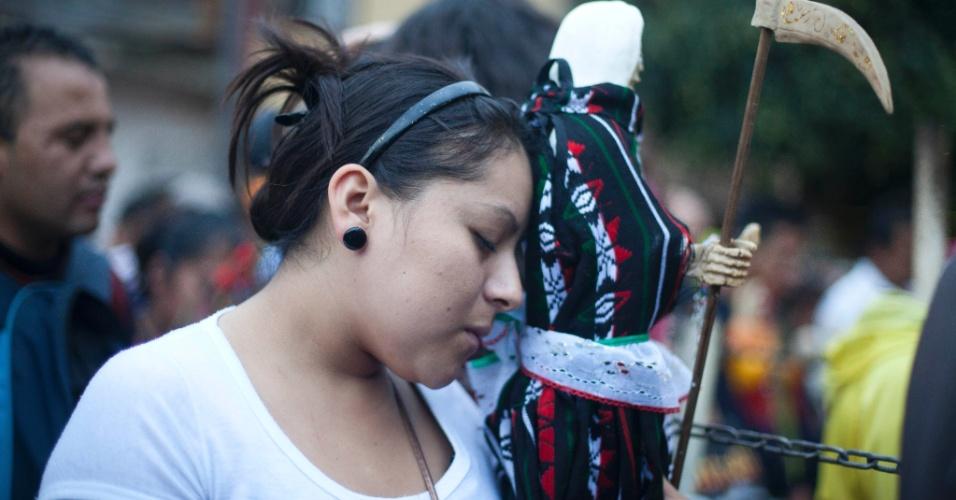"""1º.nov.2012 - Mulher carrega imagem da """"Santa Morte"""", homenageada no """"Dia dos Mortos"""", em 31 de outubro, no México"""