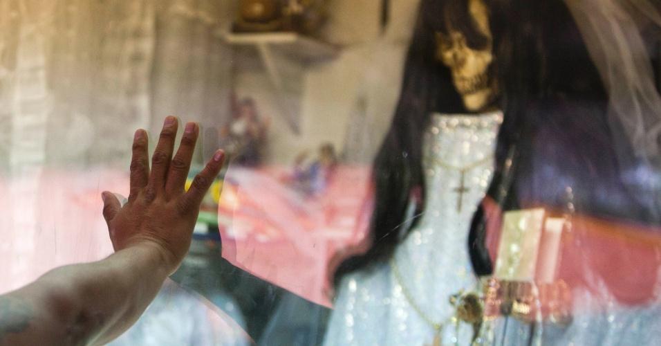 """1º.nov.2012 - Mulher toca vidro que protege a imagem da """"Santa Morte"""", homenageada no """"Dia dos Mortos"""", em 31 de outubro, no México"""