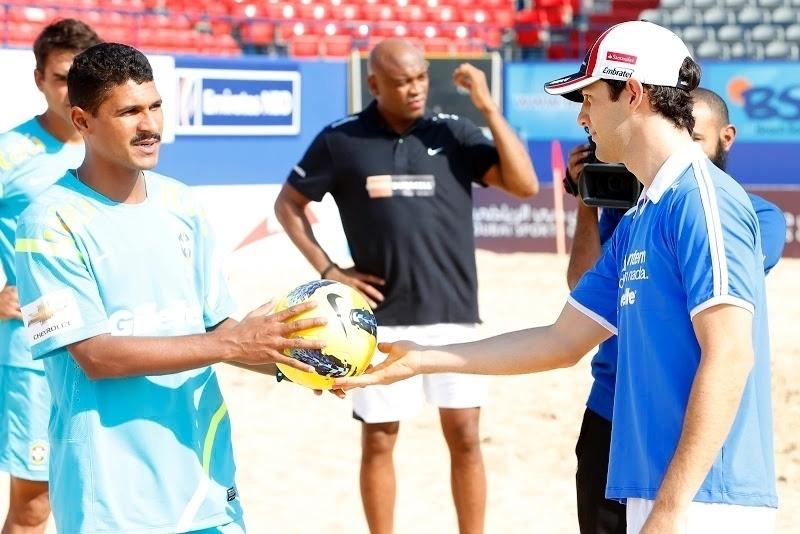 Sob olhar de Anderson Silva, Bruno Senna recebe dicas para bater pênalti durante encontro com a seleção de futebol de areia em Dubai (01/11/2012)