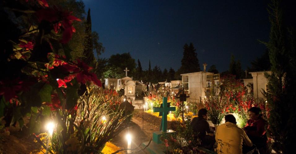 2.nov.2012 - Fiéis conversam no cemitério de San Gregório Atlapulco, na cidade do México