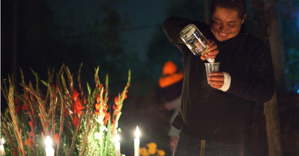 2.nov.2012 - Homem bebe durante a noite no cemitério de San Gregório Atlapulco, na cidade do México
